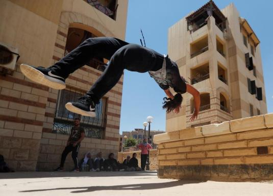 "Mariam Emad from Parkour Egypt ""PKE"" practices her parkour skills around buildings on the outskirts of Cairo"